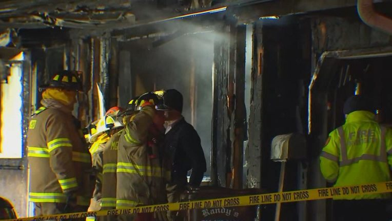 Fire investigators move through the remains of the burned-out home in Maple Grove.
